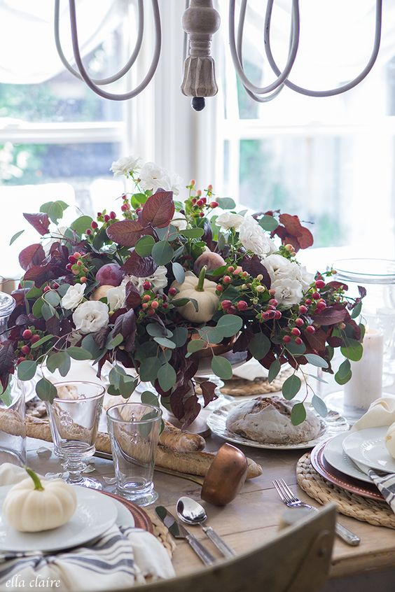 a gorgeous fall centerpiece of eucalyptus, dark foliage, berries, white blooms and pumpkins and fruit