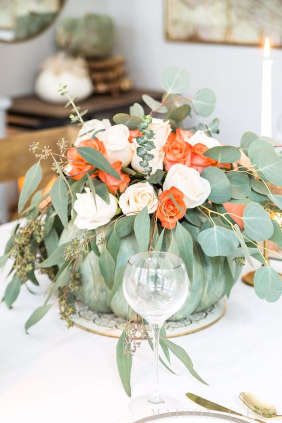 a green pumpkin with blush and orange roses and various types of eucalyptus is a natural and chic centerpiece for the fall
