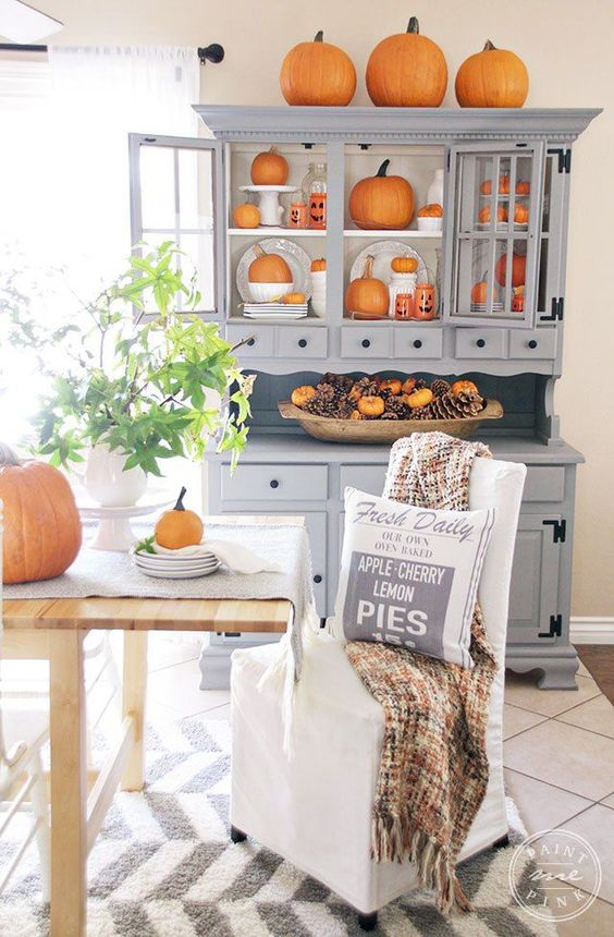 a grey buffet with lots of orange pumpkins, a dough bowl with pinecones and faux orange pumpkins
