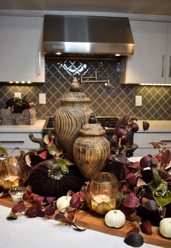 a jewel-toned fall decoration with burgundy leaves, candles, white pumpkins and wooden jars