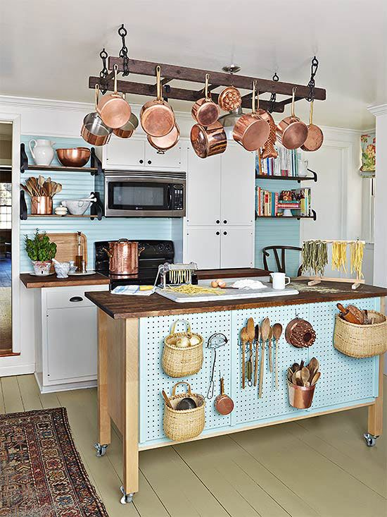 a kitchen island on wheels and with pegboard with hooks for storing stuff plus a ladder for hanging things over it