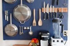 a large blue pegboard with hooks and hangers holding various pans, pots and other stuff is a great solution for a kitchen