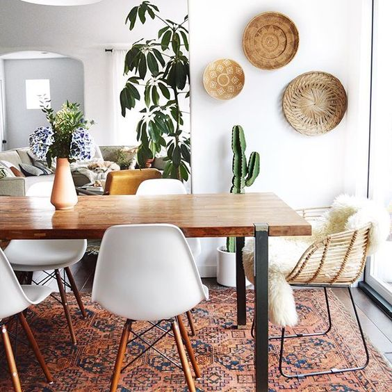 a light-filled boho dining space with decorative plates, greenery,a boho rug, white chairs and a sleek table
