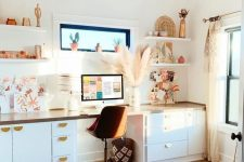 a light-filled boho home office with a desk with plenty of storage, open shelves, a boho rug, a macrame chandelier and pampas grass