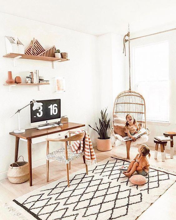 a light-filled home office with a desk and a chair, a printed rug, open shelves, a rattan hanging chair and potted greenery and pillows