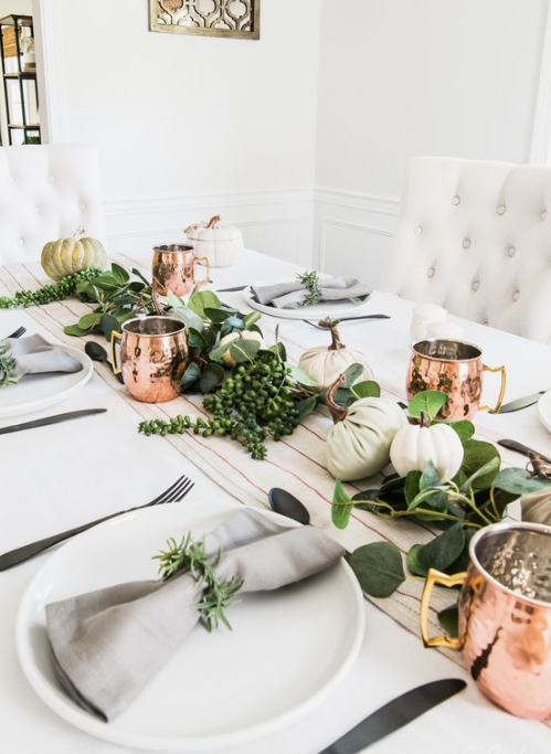 a lively fall tablescape with a striped runner, greenery and neutral pumpkin plus copper mugs
