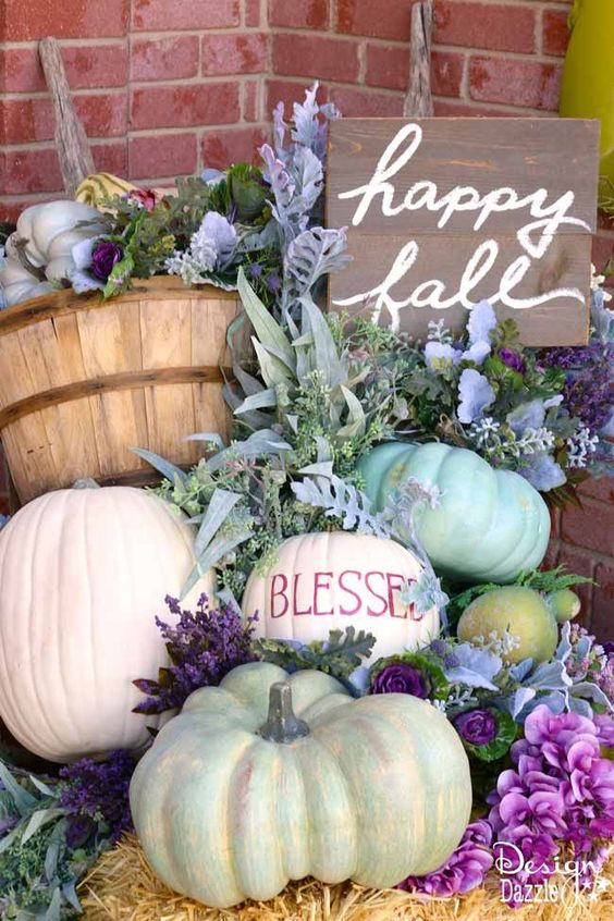 a lovely and lush fall arrangement of lots of pumpkins, greenery, bright blooms and a sign