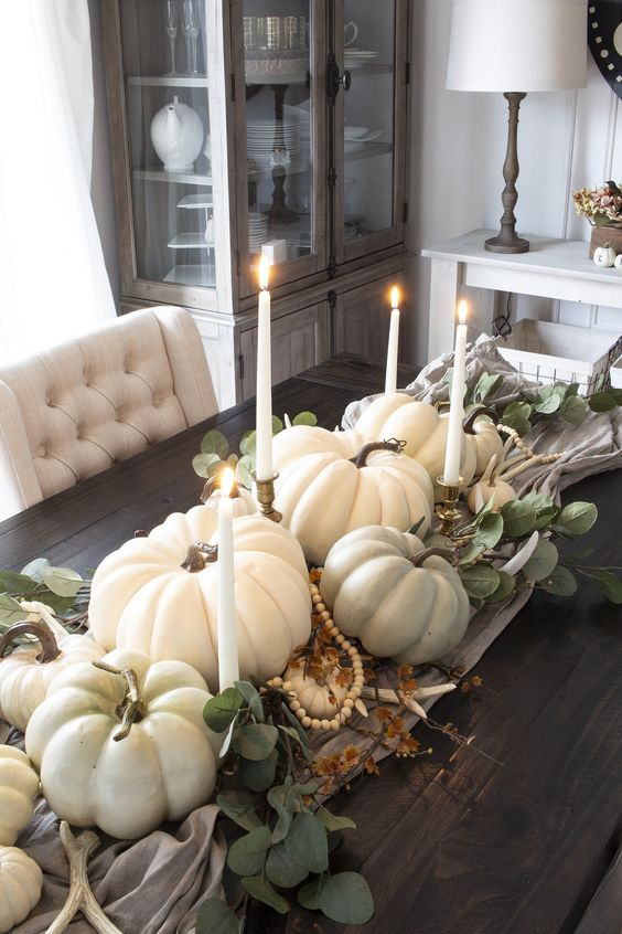 a lovely fall centerpiece of a wooden tray, white pumpkins, greenery, candles and wooden beads is very beautiful