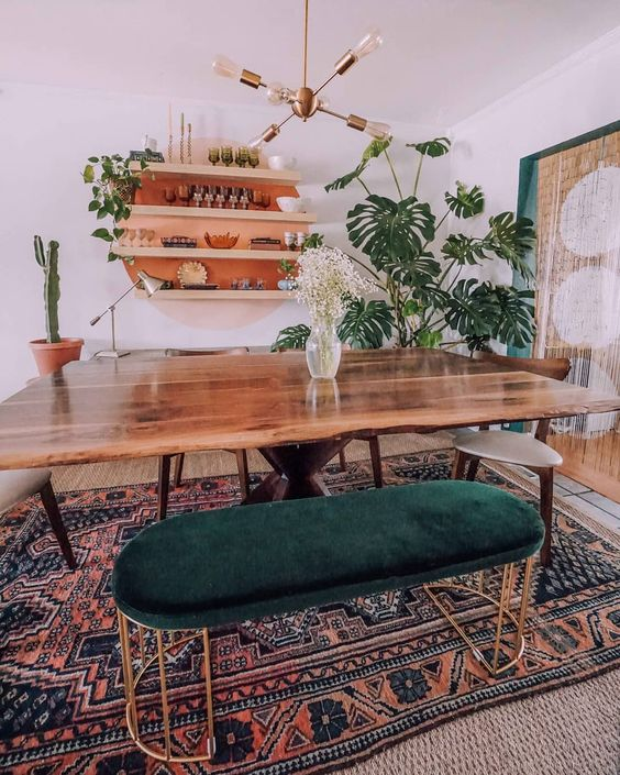 a mid century modern meets boho dining room with a live edge table, a boho rug, a forest green ottoman and potted plants