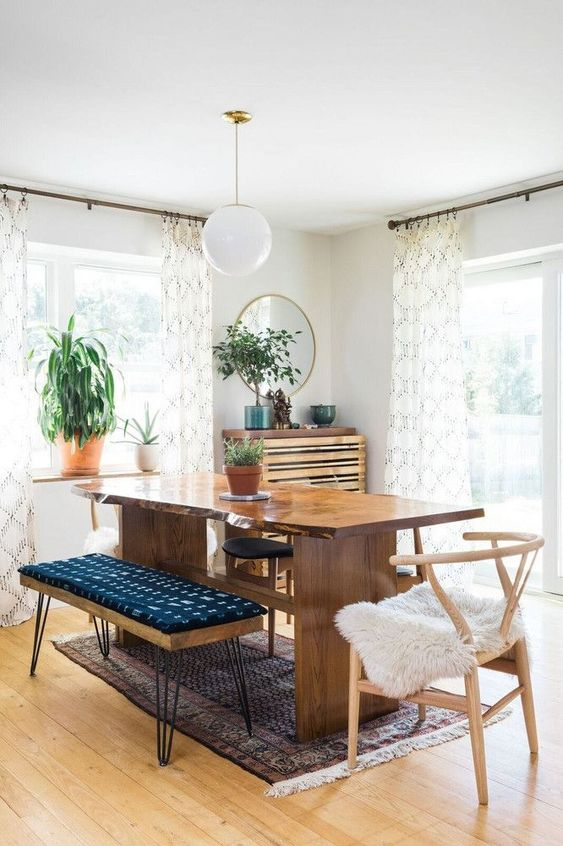 a mid-century modern meets boho dining space with a live edge table, a hairpin ottoman, potted greenery