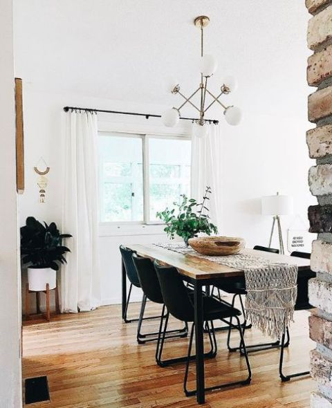 a modern boho dining room with black chairs, a sleek wooden table, a macrame table runner and greenery