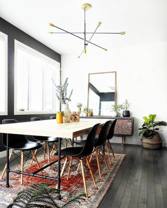 a modern boho dining space with a sleek wooden table, black chairs, a boho rug, an inlay sideboard and a catchy chandelier