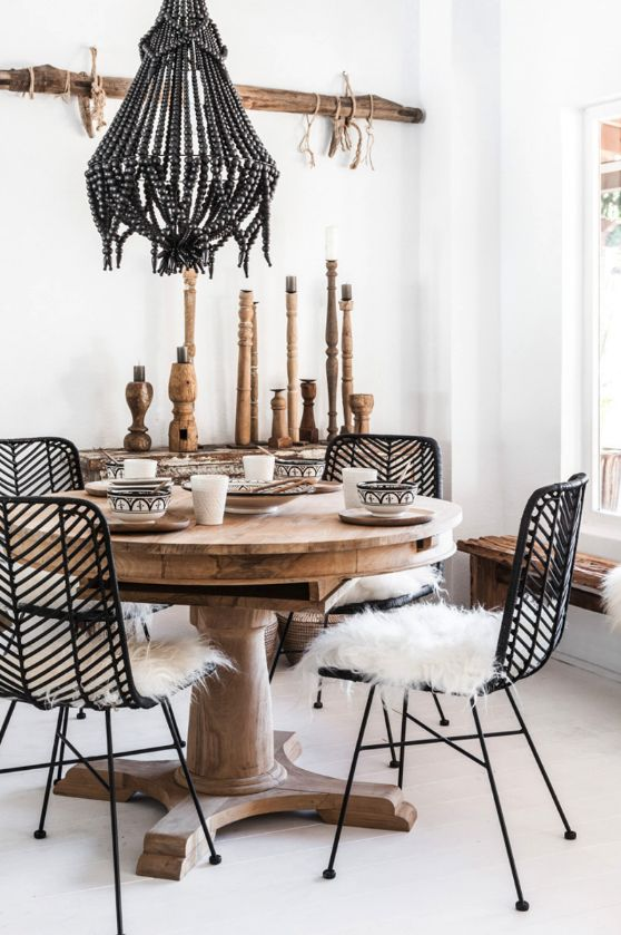 a modern meets boho dining space with a bead chandelier, rattan and wooden furniture, wooden candleholders