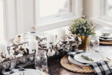 a monochromatic farmhouse tablescape with woven placemats, plaid napkins, a cotton and candle centerpiece plus greenery in a pot