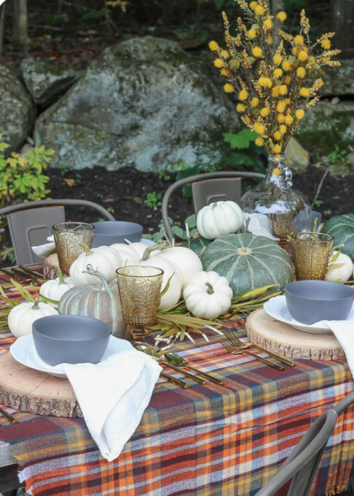 a natural fall table with a plaid tablecloth, wood slice placemats, natural pumpkins, herbs and a billy ball centerpiece