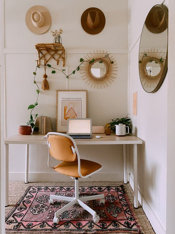 a neutral boho chic home office with a boho rug, a desk, a leather chair, hats, a rattan shelf and a sunburst mirror