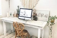 a neutral boho home office with a whitewashed desk, a unique rattan chair, a macrame hanging, potted plants and artworks