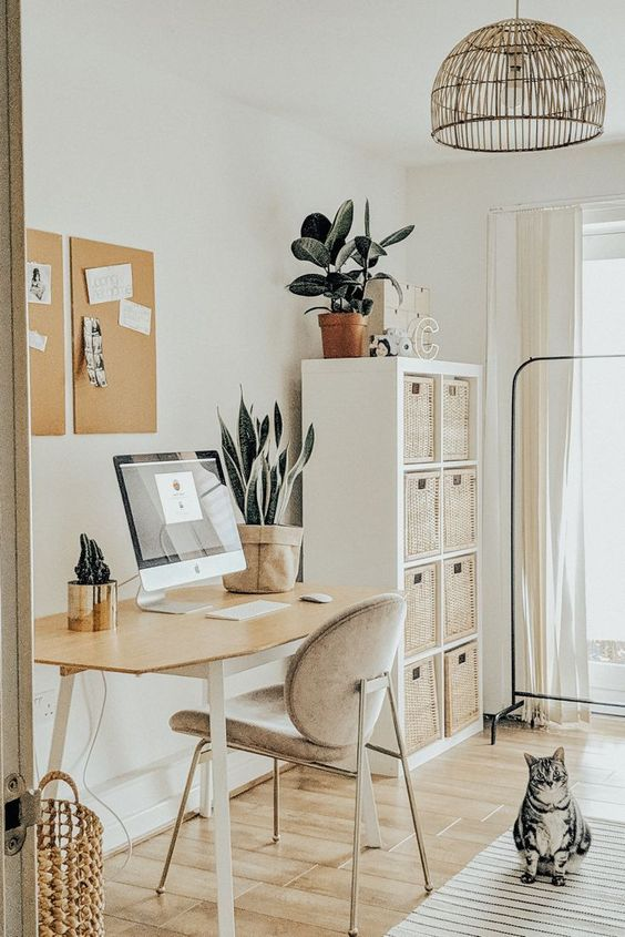 a neutral boho space with a desk, a comffy chair, a storage unit with baskets, a basket, memo boards and a a rattan chandelier