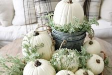 a neutral fall centerpiece of a basket with greenery, white pumpkins and a bucket with a pumpkin