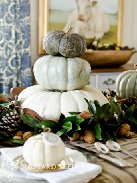a neutral fall centerpiece of magnolia leaves, nuts, pinecones and a stack of pumpkins is cool