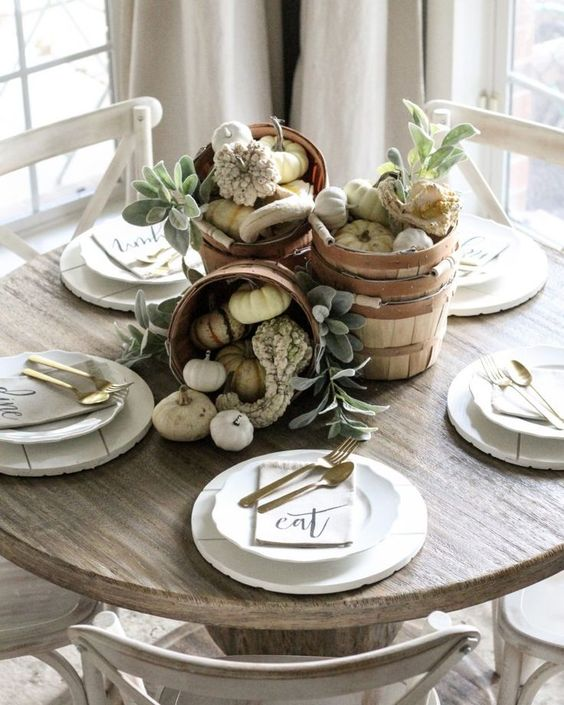 a neutral fall centerpiece of wooden baskets filled with gourds and pumpkins and neutral foliage is ethereal and cool