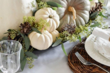 a neutral fall table setting with a bowl with natural pumpkins, greenery and pinecones, woven placemats and white porcelain