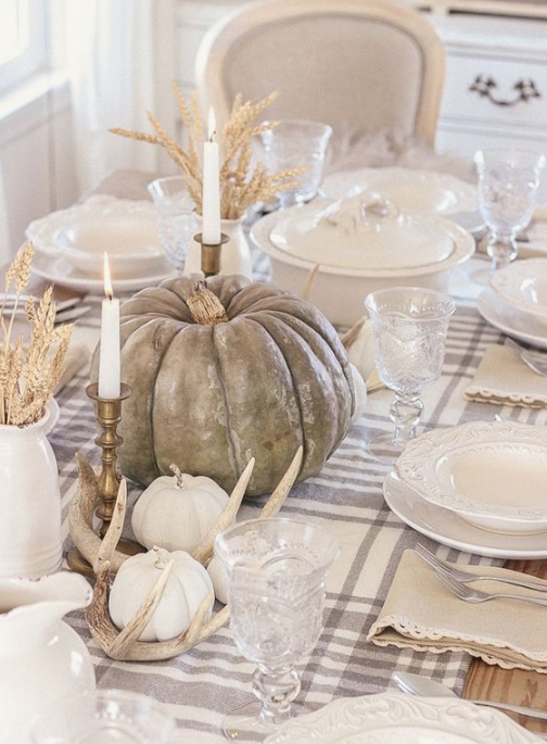 a neutral fall table with natural pumpkins, antlers, tall candles, wheat in jugs, white porcelain and a plaid table runner