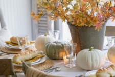 a neutral fall table with woven placemats, a fall leaf centerpiece, natural pumpkins and candles for coziness
