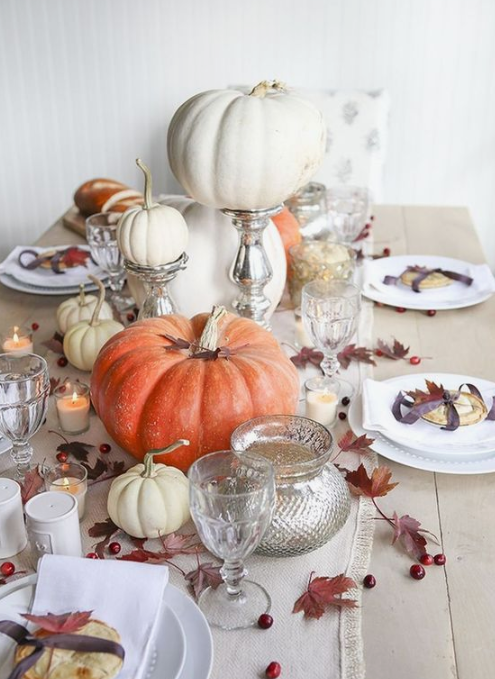 a neutral fall tablescape with a white table runner, cranberries, leaves, fresh pumpkins and candles