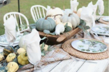 a neutral farmhouse table with woven palcemats, printed plates, natural veggies and pumpkins plus greenery