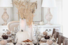 a neutral farmhouse tablescape with a lace runner, wheat arrangements, neutral pumpkins and velvet ones to mark eahc place setting