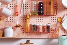 a pink pegboard hanging over the cabinets allows attaching a lot of shelves, hooks and wire holders