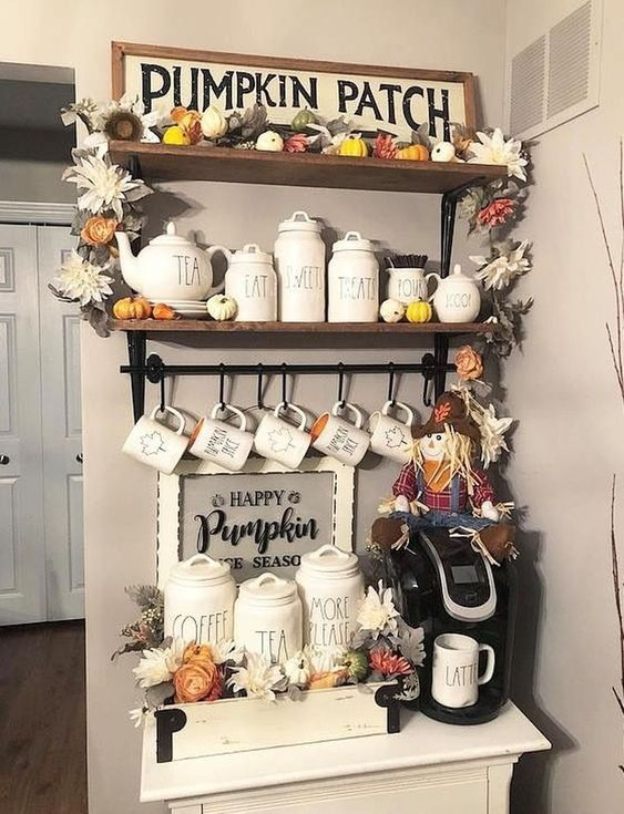 a pumpkin patch with fake flowers and leaves, a sign, a hay doll and some neutral porcelain jars