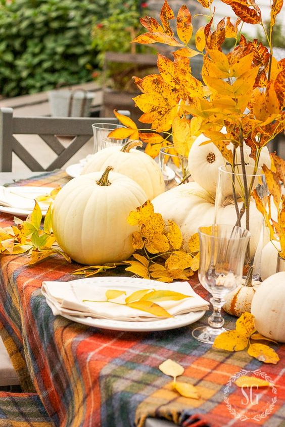 a relaxed and bright fall centerpiece of white pumpkins and bright yellow fall leaves in vases is very cool