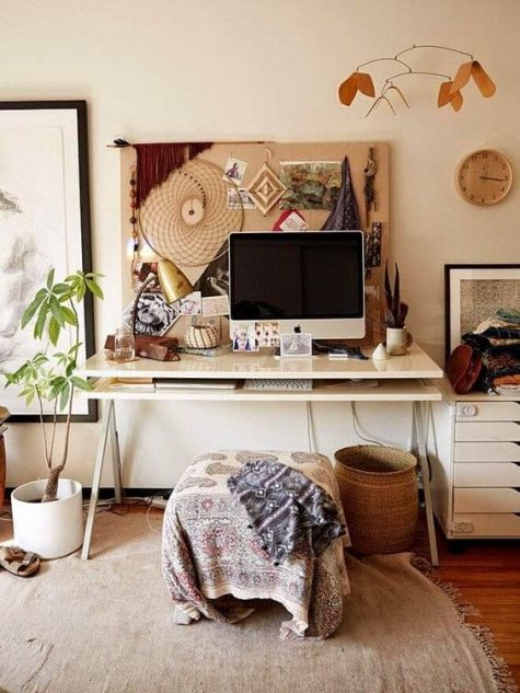 a relaxed boho office with a memo board with artworks, a boho stool and blanket, baskets and potted plants