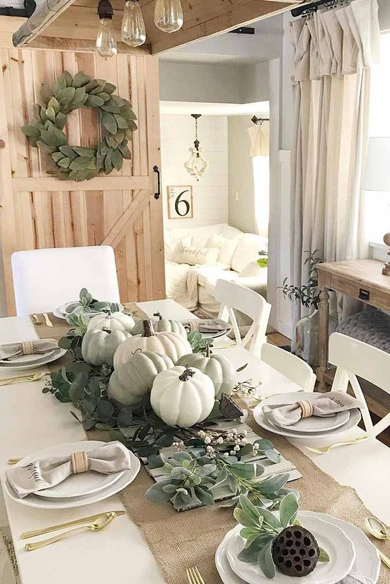 a relaxed neutral fall centerpiece of pale greenery, neutral pumpkins and wax flowers is a cool idea for your tablescape