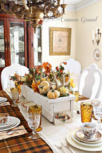 a rustic fall centerpiece of a white box with faux pumpkins, antlers, bold leaves and vine is vintage and elegant