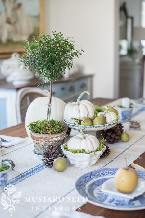 a rustic fall centerpiece of white pumpkins, pears, moss, a potted tree and pinecones all around for a cool look