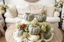 a rustic fall decoration of stacked heirloom pumpkins and green hydrangeas is a lovely centerpiece or just decoration