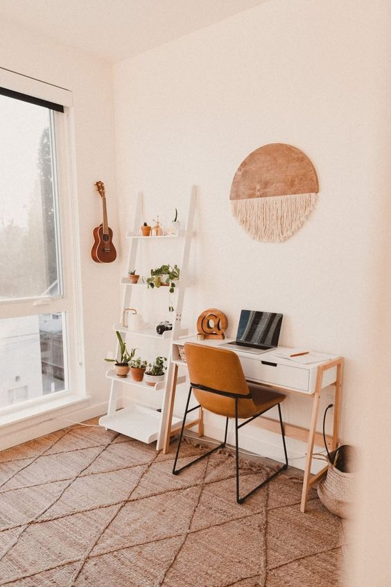 a simple and cozy boho home office with an open storage unit, a desk, a leather chair, a macrame hanging and potted plants