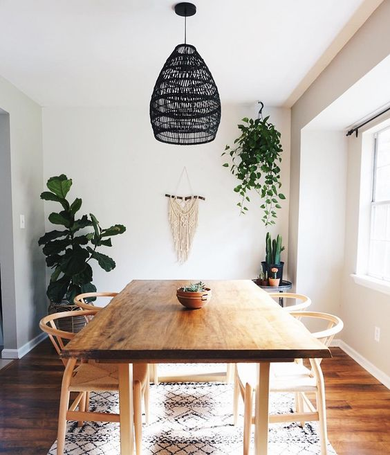 a simple boho dining room with a macrame hanging, a black wicker pendant lamp, wooden furniture and potted greenery and cacti