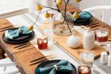 a simple fall tablescape with dark plates, blue napkins, a branch and pear centerpiece and white vases with wheat