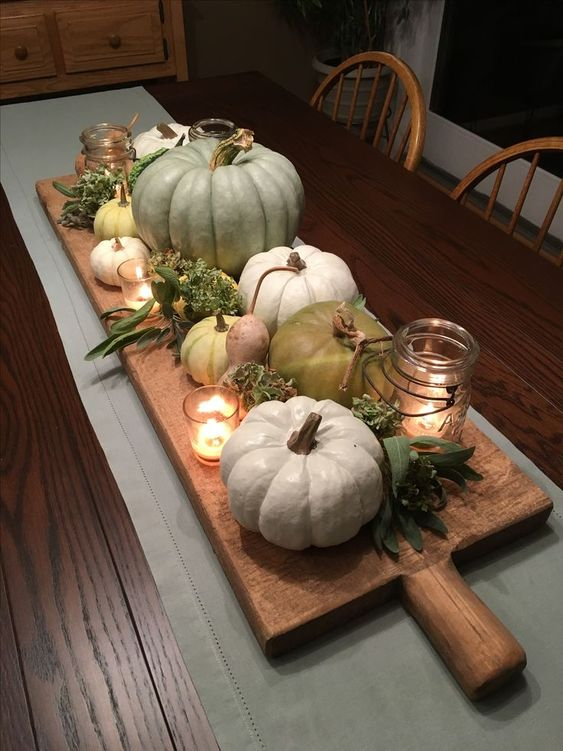 a simple farmhouse centerpiece of a wooden board with pumpkins, gourds, greenery, candles is lovely