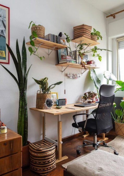 a small boho home office with a simple wooden desk, floating shelves, potted succulents and plants, baskets