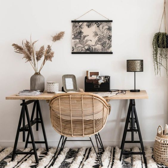 a stylish boho home office nook with a trestle desk, a rattan chair, potted plants and pampas grass, a graphic wall hanging