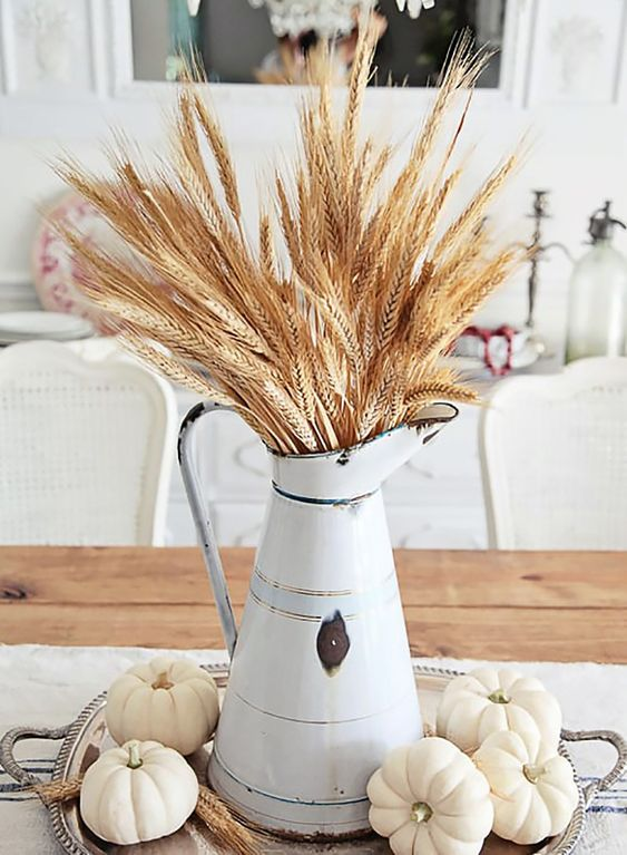a stylish farmhouse fall centerpiece with a metal jug with wheat and white pumpkins on a silver tray