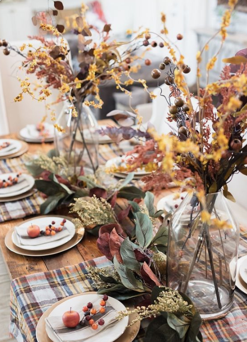 a super natural fall tablescape with plaid placemats, berries, fruits, foliage and dried herbs and blooms in vases