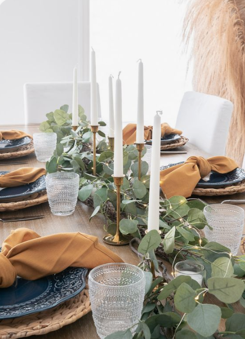a very simple fall tablescape with a greenery and lights runner, tall candles, woven placemats, blue plates and rust napkins