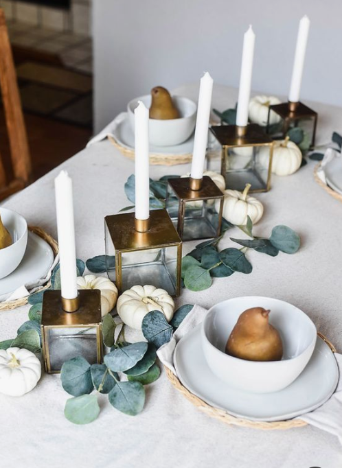 a very siple yet elegant fall tablescape with greenery, white pumpkins, candles in gold candleholders and pears for each palce setting