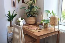 a welcoming boho nook with a desk, a wooden chair, potted plants, lights, a rattan lamp and baskets is very cozy and warming
